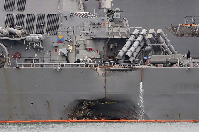 This Aug. 22, 2017 file photo shows the damaged port aft hull of the USS John S. McCain while docked at Singapore's Changi naval base. (AP Photo/Wong Maye-E)
