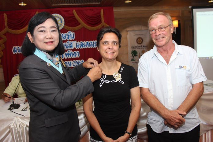 DG Onanong inducts Margaret Grainger into the Rotary Club of Pattaya as her proposer Stephen Devereux looks on.
