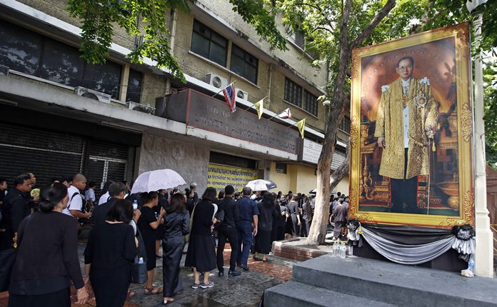 Mourners line up beside a of portrait of HM the late King Bhumibol Adulyadej to pay their respects to the Royal Urn outside the Grand Palace for last day of viewing in Bangkok, Thursday, Oct. 5, 2017. The royal cremation is scheduled on Oct. 26, 2017. Adulyadej died on Oct. 13 last year at age 88 after seven decades on the throne. (AP Photo/Sakchai Lalit)