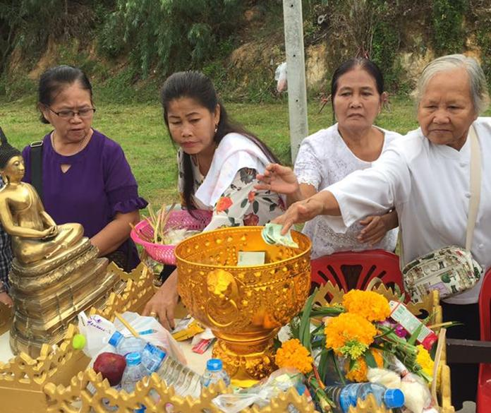 People take part in alms giving at Wat Boonsampan.