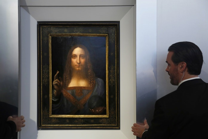 """Security guards open a door to reveal """"Salvator Mundi"""" by Leonardo da Vinci during a news conference at Christie's in New York, Tuesday, Oct. 10. (AP Photo/Seth Wenig)"""