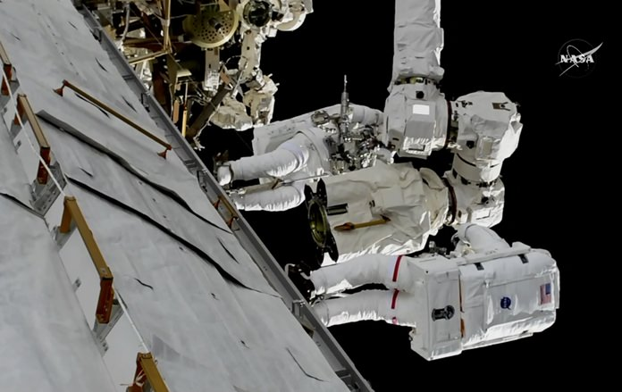 In this frame from NASA TV, Astronauts Mark Vande Hei and Randy Bresnik, bottom, work on the International Space Station on Thursday, Oct. 5, 2017. The astronauts went out on a spacewalk to give the International Space Station's big robot arm a new hand. (NASA TV via AP)