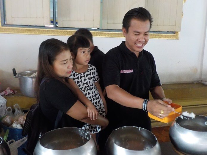 A family makes merit with tam bon in Pattaya.
