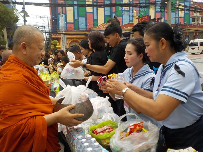Presenting morning alms to monks in Pattaya City.