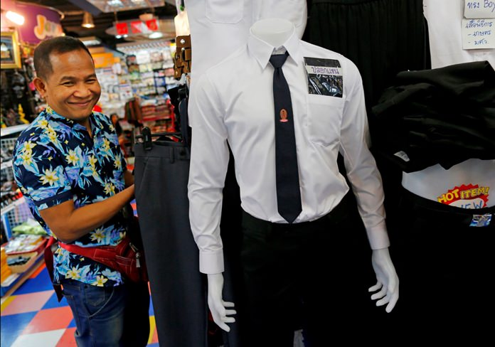 Clothing retailer Pirumchai Asiram tidies up black shirts for sale as he starts another day of business in Bangkok. (AP Photo/Wally Santana)