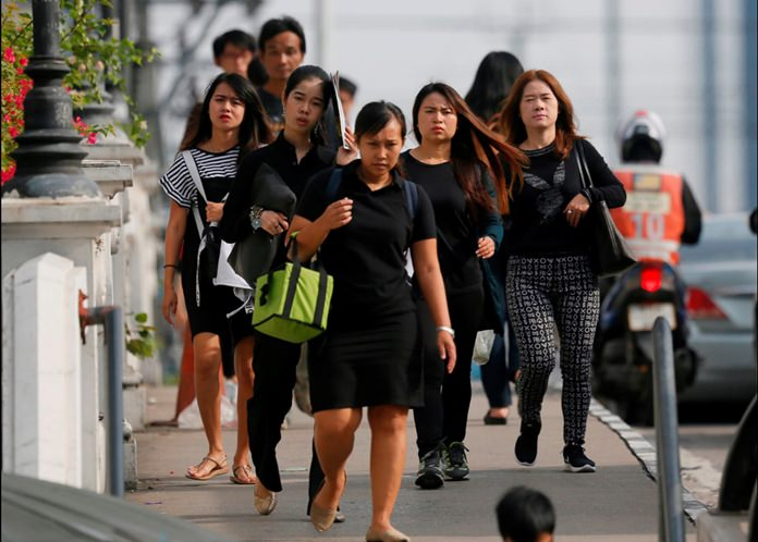 Morning commuters cross a bridge in Bangkok dressed in black in honor of His Majesty the late King. (AP Photo/Wally Santana)