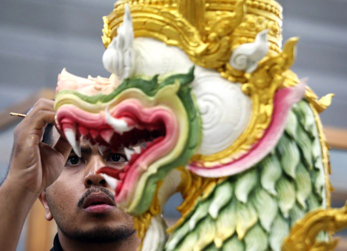 An artist paints a creature from ancient epics to decorate the royal crematorium and funeral complex. (AP Photo/Sakchai Lalit)