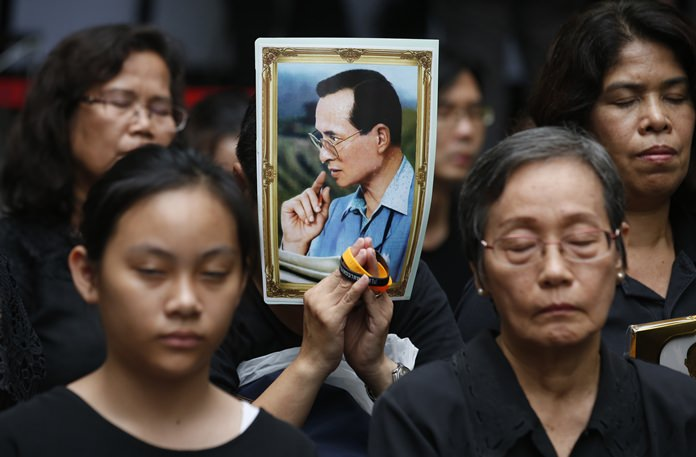 Mourners hold a portrait of His Majesty the late King Bhumibol Adulyadej during a moment of silence at Siriraj Hospital where he died a year earlier in Bangkok. (AP Photo/Sakchai Lalit)