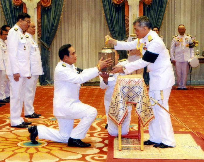HM King Maha Vajiralongkorn Bodindradebayavarangkun passes the royal fire to Thailand's Prime Minister Prayuth Chan-ocha in Bangkok. (Bureau of the Royal Household via AP)