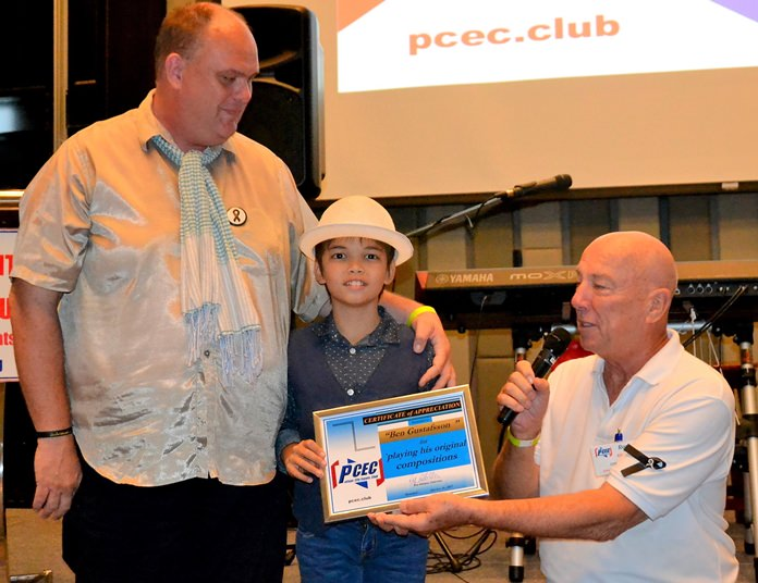 MC Roy Albiston presents Ben Rudolf with the PCEC's Certificate of Appreciation for his musical presentation as Marcus Tristan looks on.