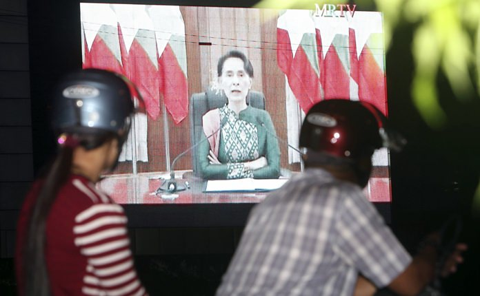 People on a motorbike watch a televised speech by Myanmar's State Counsellor Aung San Suu Kyi, by a roadside Thursday, Oct. 12, in Naypyitaw, Myanmar. (AP Photo/Aung Shine Oo)
