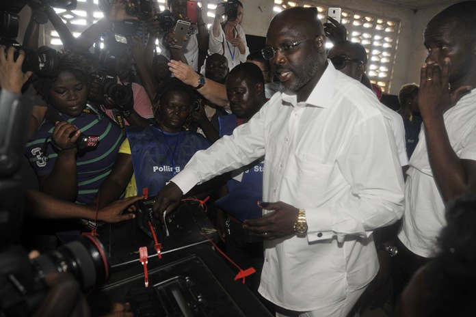 In this Tuesday, Oct. 10, 2017, file photo, former soccer star George Weah, casts his vote during the presidential election in Monrovia, Liberia. (AP Photo/Abbas Dulleh)