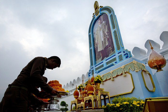 Mourners pay respects in front of a portrait of His Majesty the late King Bhumibol Adulyadej outside the Grand Palace in Bangkok, Friday, Oct. 13. (AP Photo/Gemunu Amarasinghe)