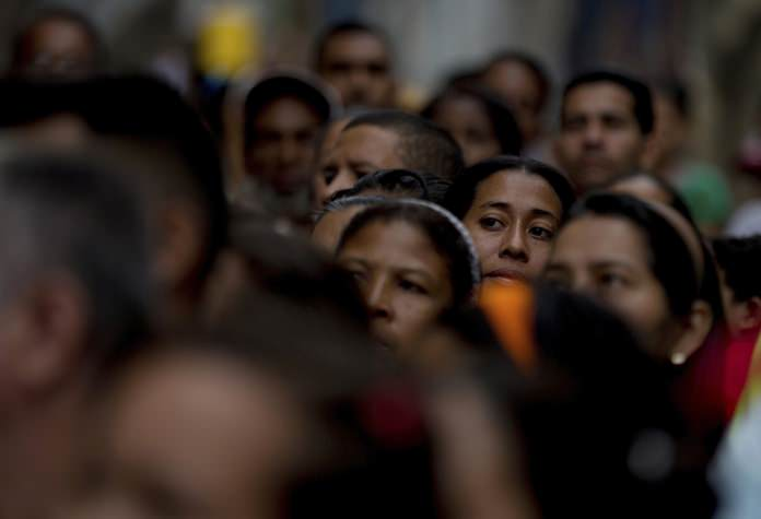 Voters wait in line to cast their ballots outside a polling station during regional elections in Caracas, Venezuela, Sunday, Oct. 15, (AP Photo/Fernando Llano)