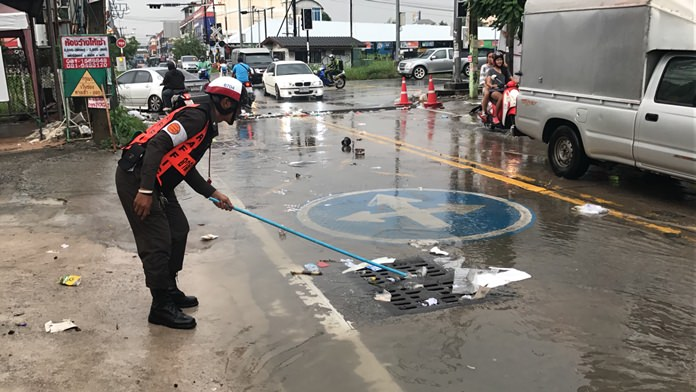 Police volunteer Prasert Tienyi attempts to clear debris from a drain on Soi Khao Noi during a heavy rainstorm, Oct. 9.