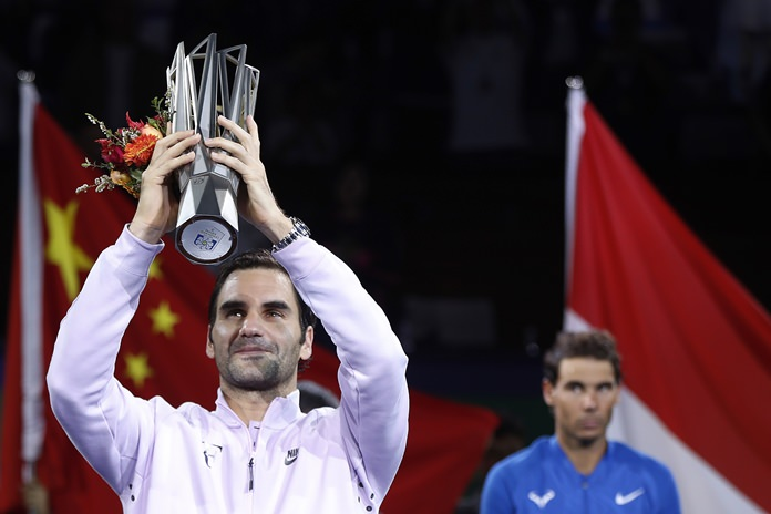 Roger Federer of Switzerland lifts the champion's trophy after defeating Rafael Nadal, right, of Spain in their men's singles final at the Shanghai Masters tennis tournament in Shanghai, China, Sunday, Oct. 15. (AP Photo/Andy Wong)