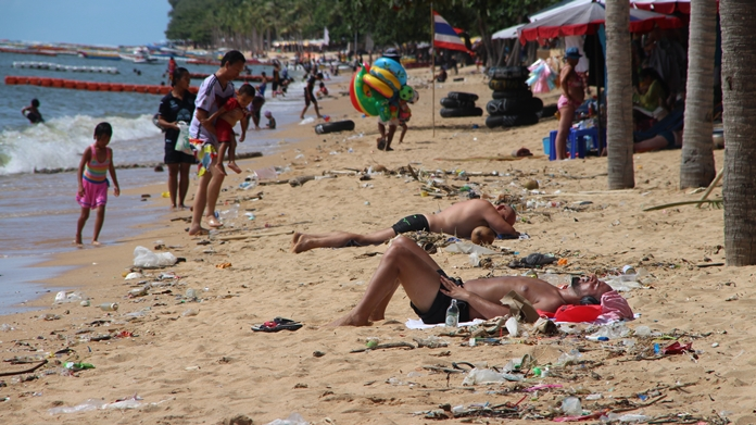 Tourists share a spot in the sun with washed-up garbage on Jomtien Beach in Pattaya, Monday, October 16.