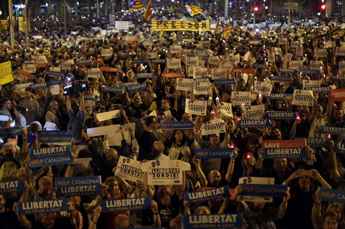 Holding signs reading in Catalan 'freedom', people gather to protest against the National Court's decision to imprison civil society leaders without bail, in Barcelona, Spain, Tuesday, Oct. 17. (AP Photo/Emilio Morenatti)