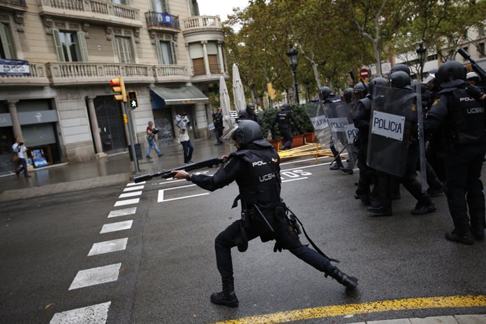 Spanish riot police shoots rubber bullet into crowds of people trying to reach a voting site in Barcelona, Spain, Sunday, 1 Oct. (AP Photo/Emilio Morenatti)