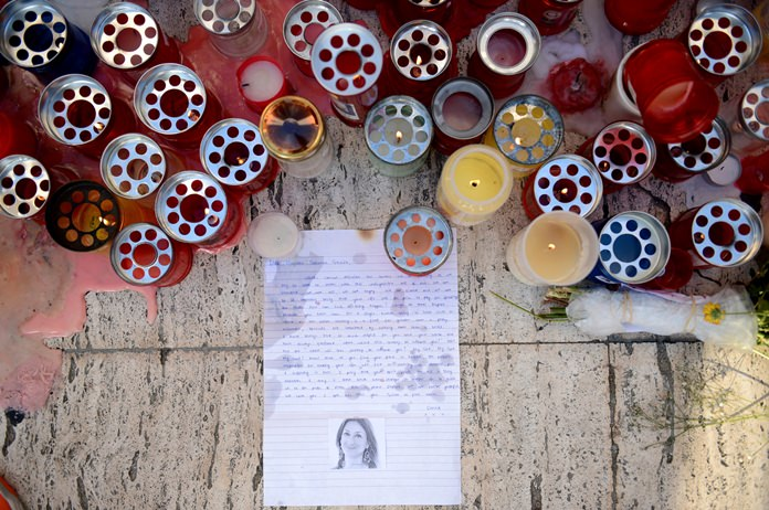 Candles, notes and paper cuttings lie next to the Love Monument in St. Julian, Malta, Tuesday Oct. 17, 2017, the day after the killing of journalist Daphne Caruana Galizia. (AP Photo/ Rene Rossignaud)
