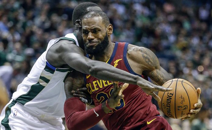 Milwaukee Bucks' Thon Maker, left, reaches in on Cleveland Cavaliers' LeBron James during the first half of their NBA basketball game Friday, Oct. 20, in Milwaukee. (AP Photo/Tom Lynn)