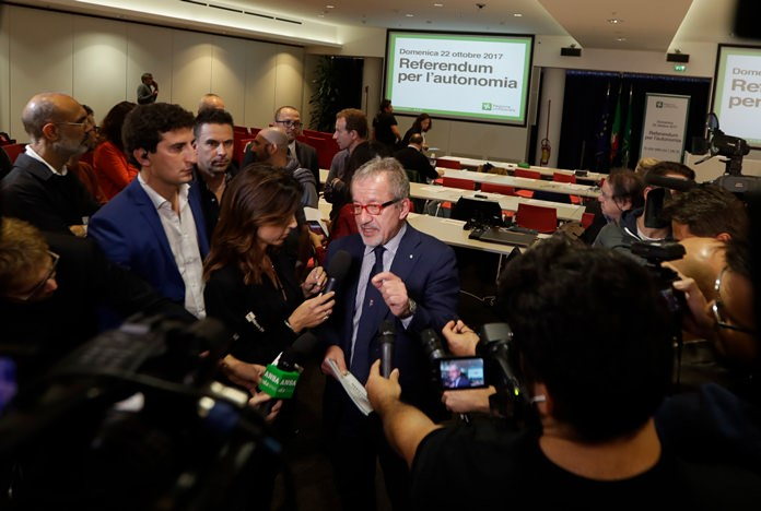 Lombardy Region President Roberto Maroni, center, answers reporter's questions at the Lombardy Region headquarters in Milan, Italy, Sunday, Oct. 22. (AP Photo/Luca Bruno)