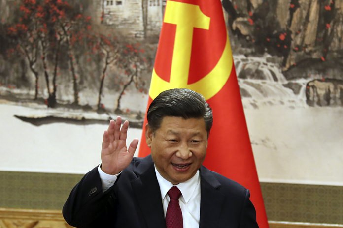 Chinese President Xi Jinping waves while addressing the media as he introduced new members of the Politburo Standing Committee at Beijing's Great Hall of the People Wednesday, Oct. 25. (AP Photo/Ng Han Guan)