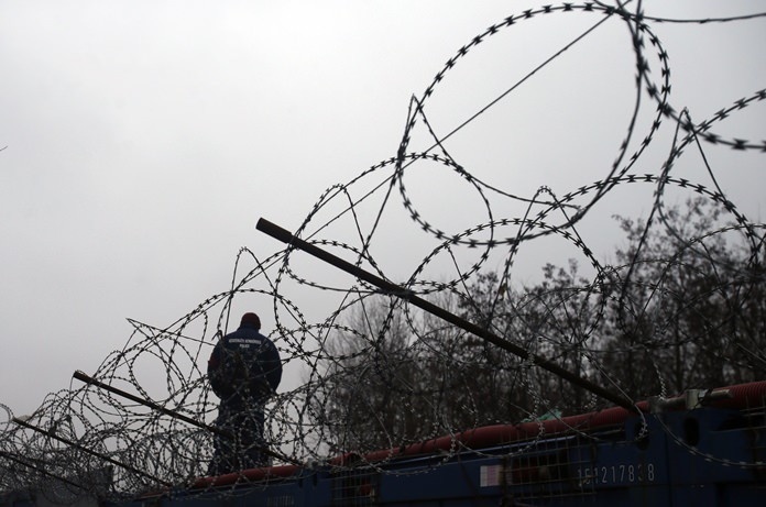A Hungarian police officer stands guard at Serbia's border with Hungary near a makeshift camp for migrants in Horgos, Serbia. (AP Photo/Darko Vojinovic)