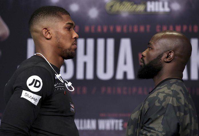 Britain's Heavyweight Champion Anthony Joshua, left, and challenger Carlos Takam face-off during the press conference at the National Museum in Cardiff Wales on Thursday Oct. 26. Joshua will take on Takam in a world title fight in Cardiff on Saturday. (Nick Potts/PA via AP)