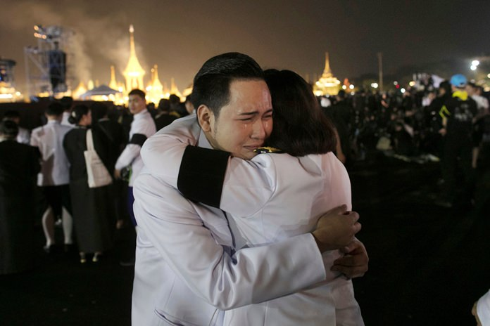 Thai officials hug as smoke rises from the royal crematorium in Bangkok, early Friday, Oct. 27. (AP Photo/Wason Wanichakorn)