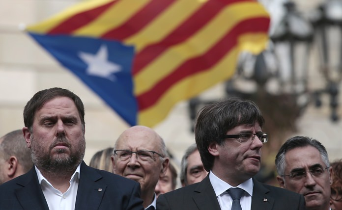 Catalan regional Vice-President, Oriol Junqueras, left, and Catalan President, Carles Puigdemont, attend during a protest called by pro-independence outside of the Palau Generalitat in Barcelona, Spain, Monday, Oct. 2. (AP Photo/Manu Fernandez)