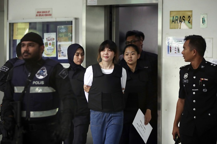 Vietnamese Doan Thi Huong, center, is escorted by police as she leaves after the court hearing at Shah Alam court house in Shah Alam, outside Kuala Lumpur, Malaysia, Monday, Oct. 2. (AP Photo/Daniel Chan)