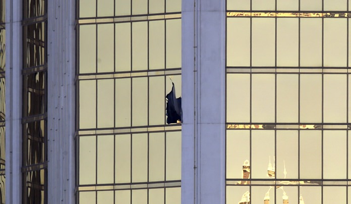 A broken window is seen at the Mandalay Bay resort and casino Monday, Oct. 2, on the Las Vegas Strip following a mass shooting at a country music festival. (AP Photo/Chris Carlson)