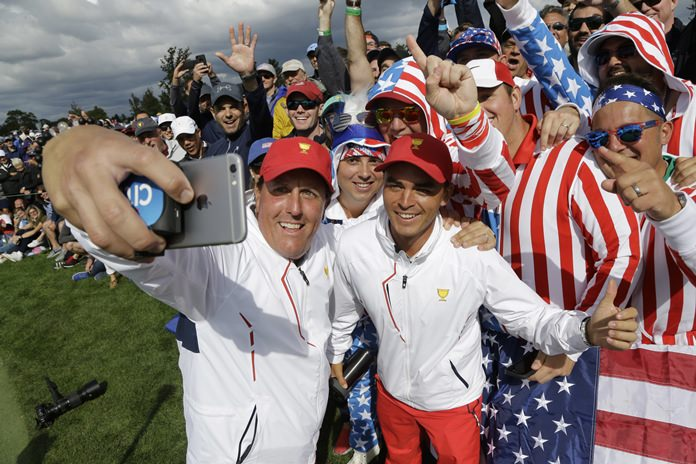 The United States' Phil Mickelson, left and Rickie Fowler take a selfie with fans on the eighth hole during the third day of the Presidents Cup at Liberty National Golf Club in Jersey City, N.J., Saturday, Sept. 30. (AP Photo/Julio Cortez)
