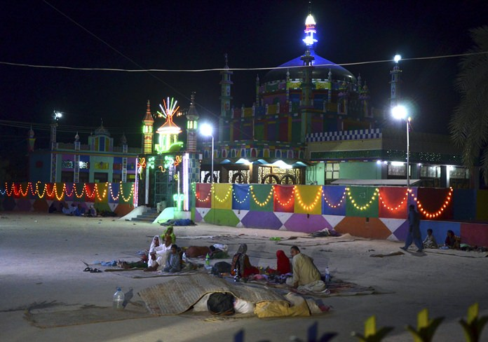 Worshippers sit outside a shrine after a bomb blast in Jhal Magsi, about 400 kilometers east of Quetta, Pakistan, Thursday, Oct. 5. (AP Photo/Abdul Hameed)