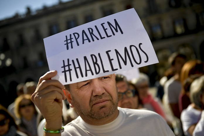 A man holds up sign reading in Spanish and Catalan language, ''We Talk'', as he takes part in a rally calling to find a solution for the crisis with Catalonia's secession at Plaza España square, in the Basque city of Vitoria, northern Spain, Saturday, Oct. 7. (AP Photo/Alvaro Barrientos)
