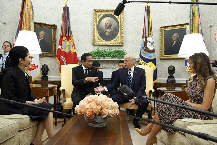 President Donald Trump shakes hands with Thai Prime Minister Prayuth Chan-ocha as his wife Naraporn Chan-ocha, left, and first lady Melania Trump watch during a meeting in the Oval Office of the White House, Monday, Oct. 2, 2017, in Washington. (AP Photo/Evan Vucci)