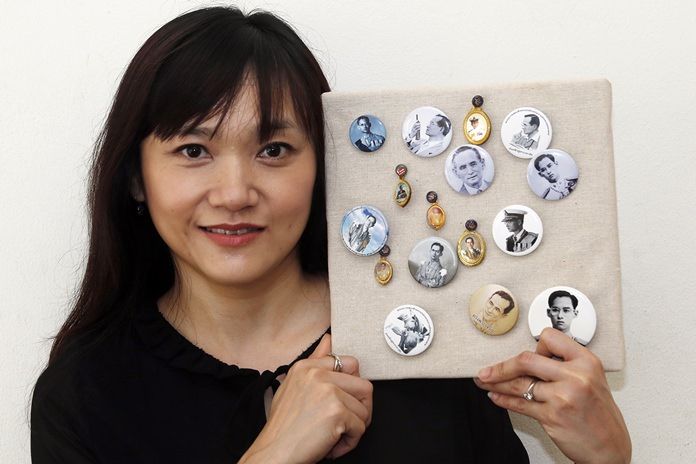 Tassanee Keenguen, a flight attendant, 47, poses with her collection of pins bearing the image of late Thai King Bhumibol Adulyadej. (AP Photo/Sakchai Lalit)