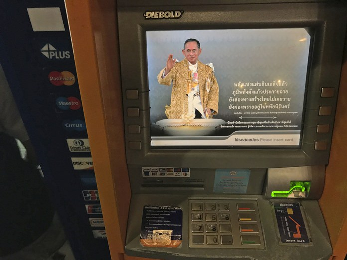 The image of the late Thai King Bhumibol Adulyadej is seen on an ATM machine. (AP Photo/Charles Dharapak)
