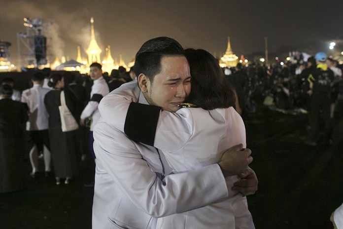 Officials hug as smoke rises from the royal crematorium of HM the late King Bhumibol Adulyadej. (AP Photo/Wason Wanichakorn)