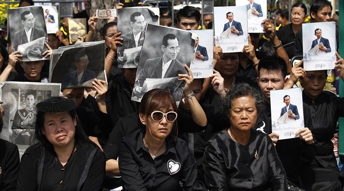 Mourners hold aloft the portraits of late Thai King Bhumibol Adulyadej during his funeral procession and royal cremation ceremony, in Bangkok, Thursday, Oct. 26, 2017. Tearful Thais clad in black mourned on Bangkok's streets or at viewing areas around the nation Thursday as elaborate funeral ceremonies steeped in centuries of royal tradition were held for King Bhumibol following a year of mourning. (AP Photo/Sakchai Lalit)