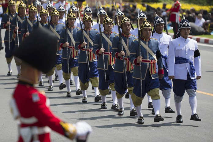 A Thai royal palace honor guard stands in attention as men in traditional attire walk in a procession moving late King Bhumibol Adulyadej's ashes to special locations for further Buddhist rites in Bangkok, Friday, Oct. 27, 2017. (AP Photo/Wason Wanichakorn)