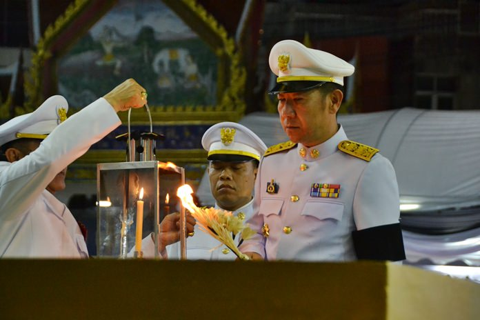 Banglamung District Chief Naris Niramaiwong begins the final part of the ceremony by lighting the sandalwood flowers to coincide with the cremation in Bangkok.