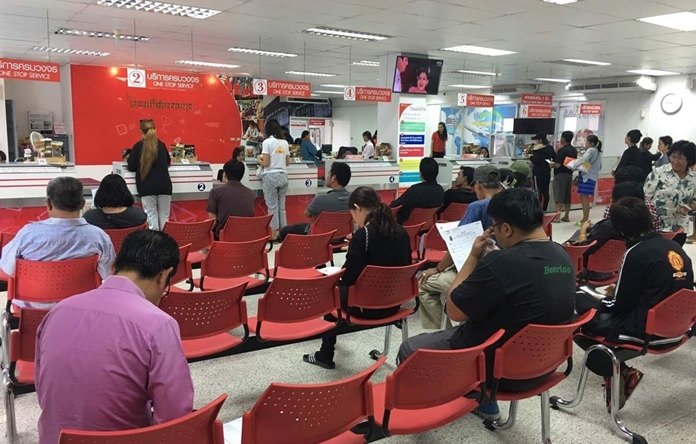 Residents queue up at Banglamung Post Office to reserve pins commemorating the cremation of King Rama IX.