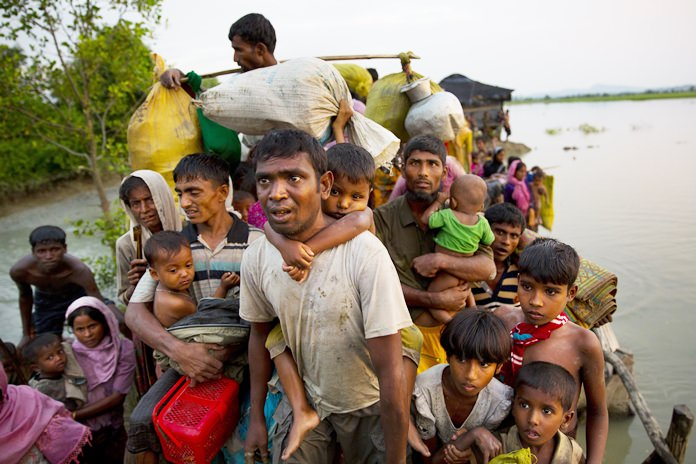 Rohingya Muslims carry their young children and belongings after crossing the border from Myanmar into Bangladesh, near Palong Khali, Bangladesh, Wednesday, Nov. 1, 2017. In a scene that's played out over and over again, at least 2,000 exhausted and starving Rohingya crossed the swollen Naf River on Wednesday and waited along the Bangladesh border for permission to cross. (AP Photo/Bernat Armangue)