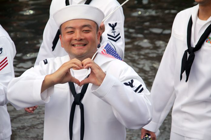 A USA sailor sends a heart signal out to Thai people.