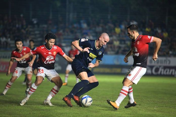 Pattaya United's Milos Stojanovic (centre) attempts to dribble the ball past BEC Tero Sasana defenders during the Thai Premier League fixture at the Nongprue Stadium in Pattaya, Saturday, Nov. 18. (Photo courtesy Pattaya United)