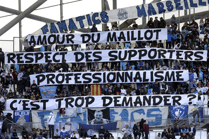 """Marseille supporters display banners reading """"Love of the jersey, respect for supporters, professionalism, is it too much to ask?"""", prior to the League One soccer match between Marseille and Caen, at the Velodrome stadium, in Marseille, southern France, Sunday, Nov. 5. (AP Photo/Claude Paris)"""