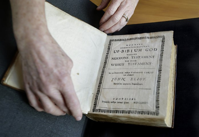 In this Thursday, Oct. 19, 2017, photo Massachusetts Institute of Technology archivist Nora Murphy places a second edition of the Eliot Indian Bible on a table at the MIT rare book collection, in Cambridge, Mass. The second edition of the Eliot Indian Bible, translated into Wampanoag, is dated 1685. Experts have relied on extensive written records in Wampanoag to reclaim the language, including 17th century phonetic translations of the King James Bible. (AP Photo/Steven Senne)