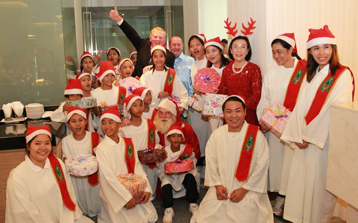 Maurice Roberts, president of the PSC waves as Khun Toy and Santa Claus pose for a group photo with the teachers and residents of the Pattaya Orphanage.